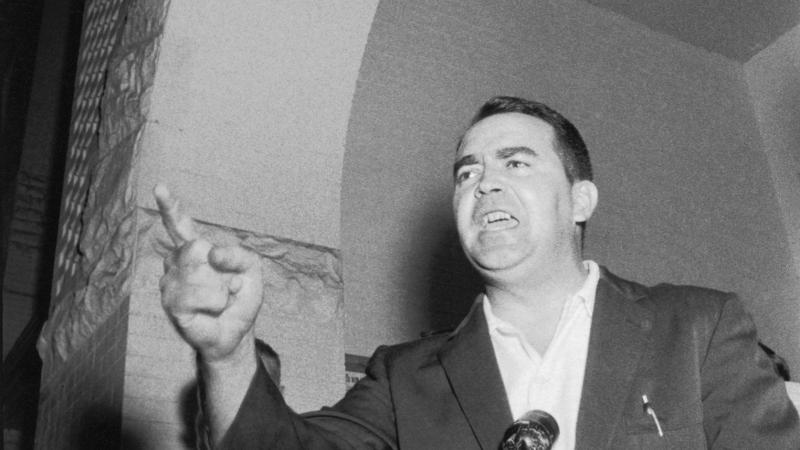 Black and white photo of Asa Carter giving an impassioned speech while gesturing with his finger.