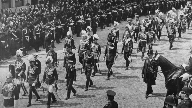 Black and white photo of a funeral parade for King Edward VII of England. Soldiers dressed in full regalia march in the streets.