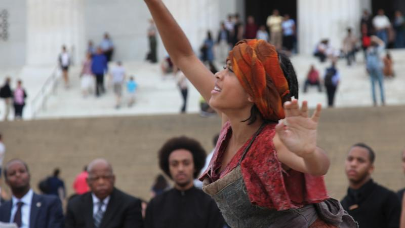 Color photo of an African-American interpretive dancer performing on the steps of the Lincoln Memorial.