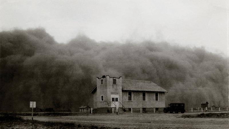 Black and white photo of a country church being engulfed by a giant dust cloud.