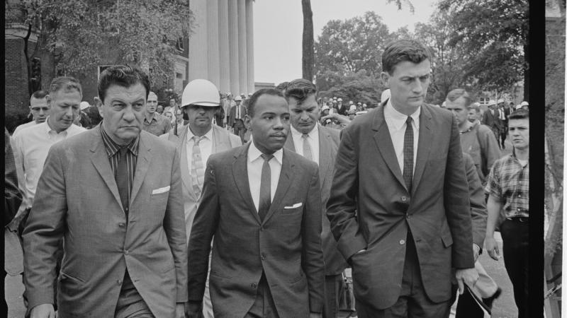 Black and white photo of bureaucrats in suits walking as an entourage.