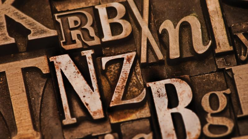 Assorted letters in shades of brown, on a bronze background