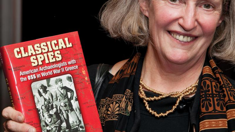 "Heuck Allen in a striped scarf, posing with her book ""Classical Spies"""