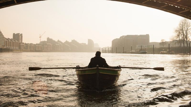 Silhouetted photo of Irons rowing a boat on the Thames, underneath a bridge