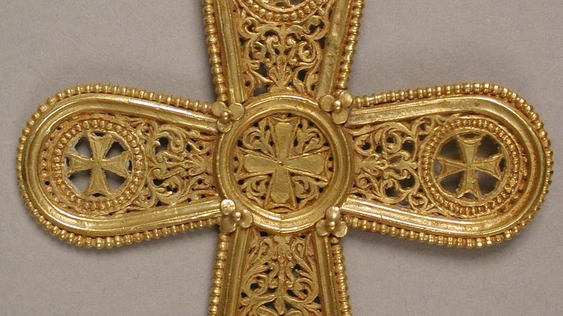 A gold pendant in the shape of a cross, with rounded edges and intricate filigree designs