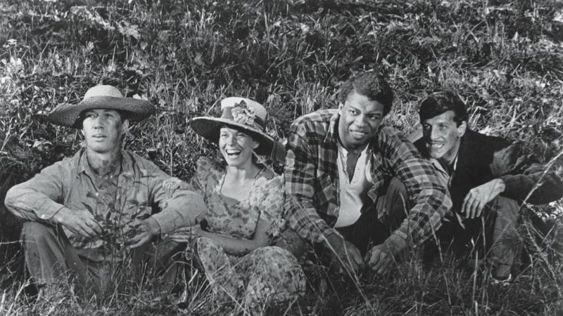 4 of Boxcar Bertha's characters, sitting a grassy field