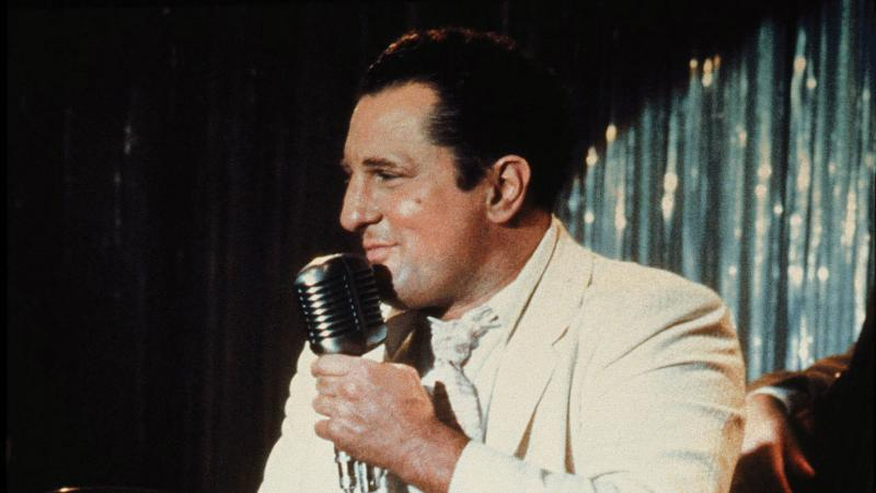 De Niro singing onstage in a white suit jacket, in a scene from Raging Bull