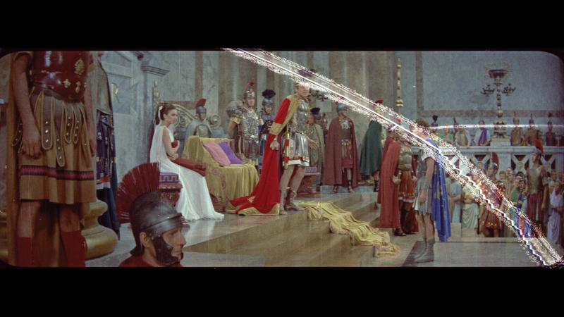 Still of Burton as a Roman emperor in court, with a white streak slanting across the right side of the still