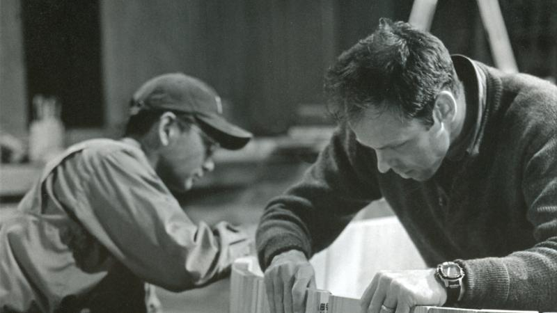 black and white photo of two men working on a piece of wood