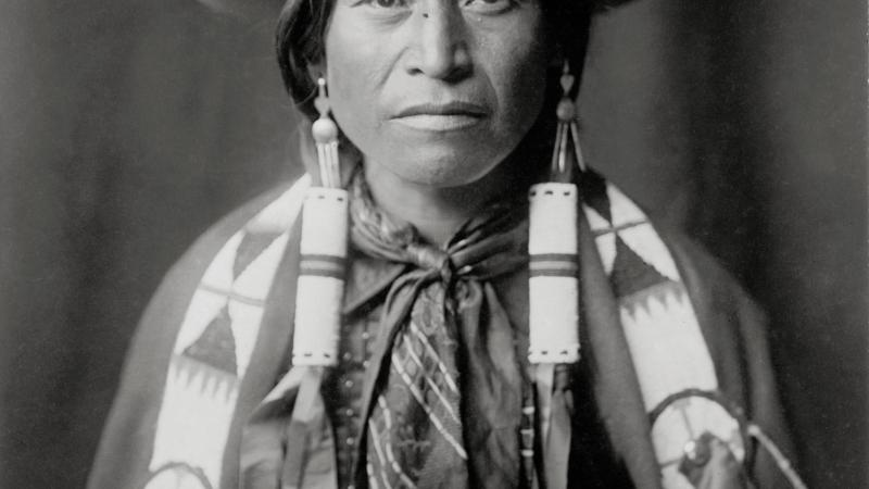 Black and white photo of apache cowboy in hat and scarf