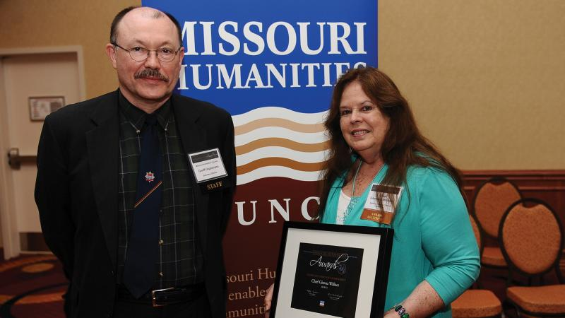 Giglierano and Wallace, posing with Wallace's award in front of a Missouri Humanities poster