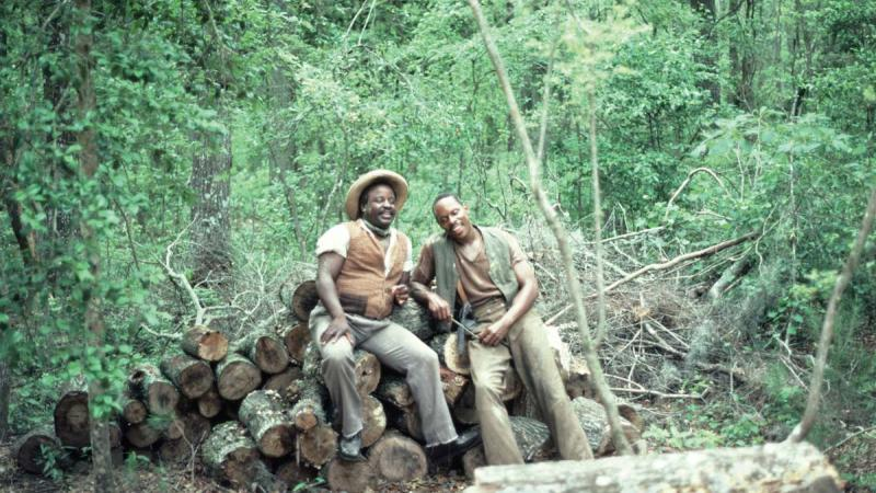 Northup and a friend rest from their labors, sitting on the pine logs they must transport, in the woods