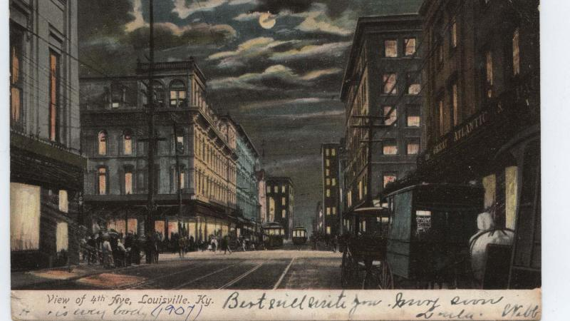 Night view of fourth avenue, with a full moon shining in a cloudy sky, lights on in the buildings