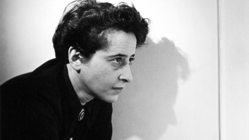 Arendt, with short dark hair, holding a cigarette, leaning on a countertop and facing to the right