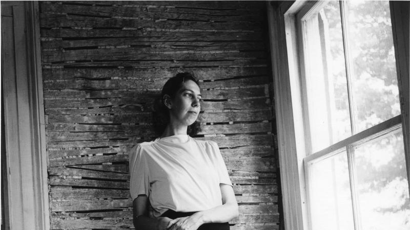 Welty in a white blouse and black skirt, leaning against a brick wall and looking out of a large window to her left