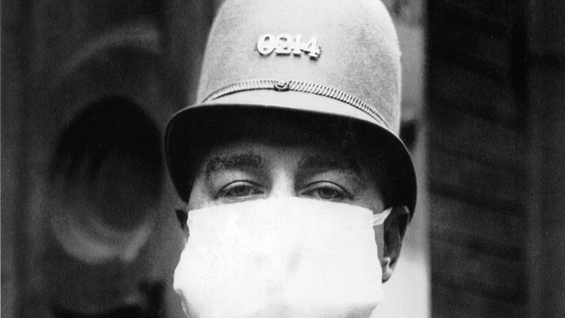 A police officer, in uniform and rounded helmet, has his entire face, other than the eyes, covered by a white cotton medical mask