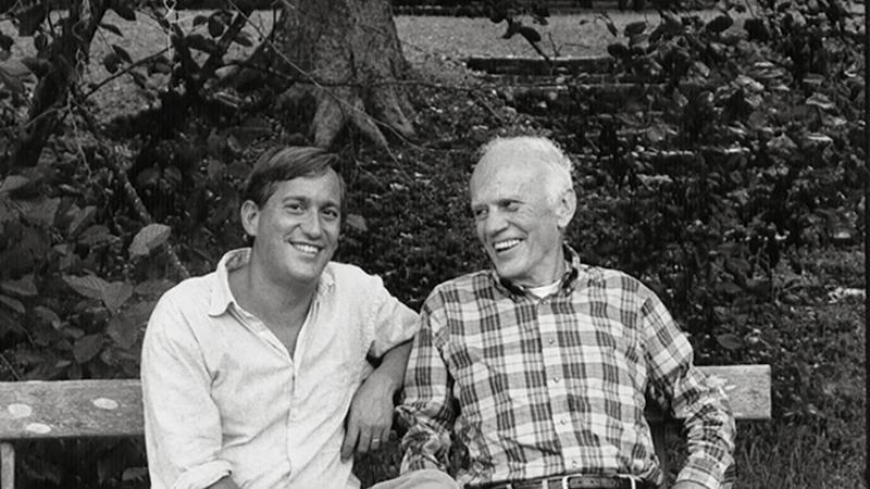 Black and white photo of Walter Isaacson and Walker Percy sitting on a bench, smiling.