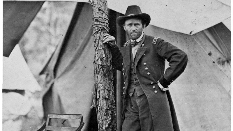 Black and white photo of General Ulysses S. Grant standing next to a tree in a military camp.