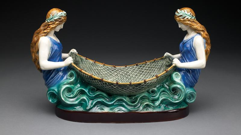 Image of a painted ceramic sculpture of two women tending a net between them.
