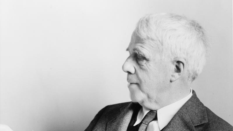 Black and white photo of Robert Frost sitting and reading a manuscript.