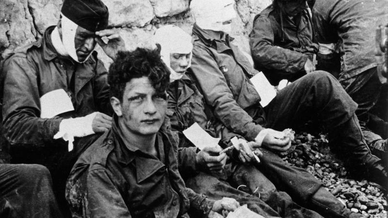Four american soldiers, three with heavy bandaging over their faces, sitting and waiting