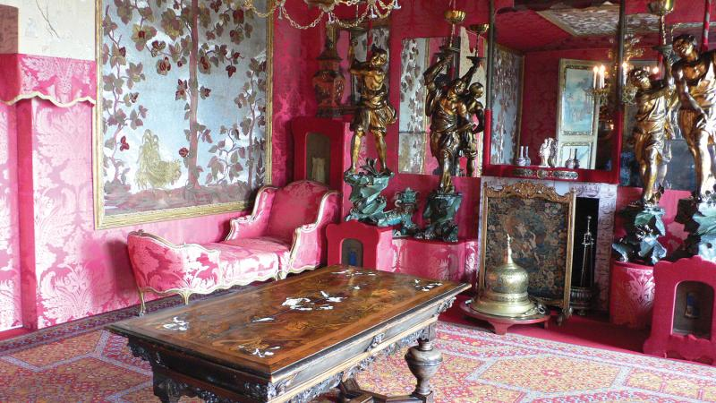 A room in Hauteville House, with bright pink walls, a large wooden table, and ornate, pink furniture