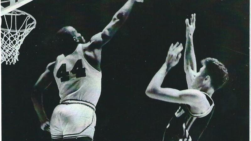 Flick shoots the basketball midjump, as Currie tries to block his shot with an outstretched arm