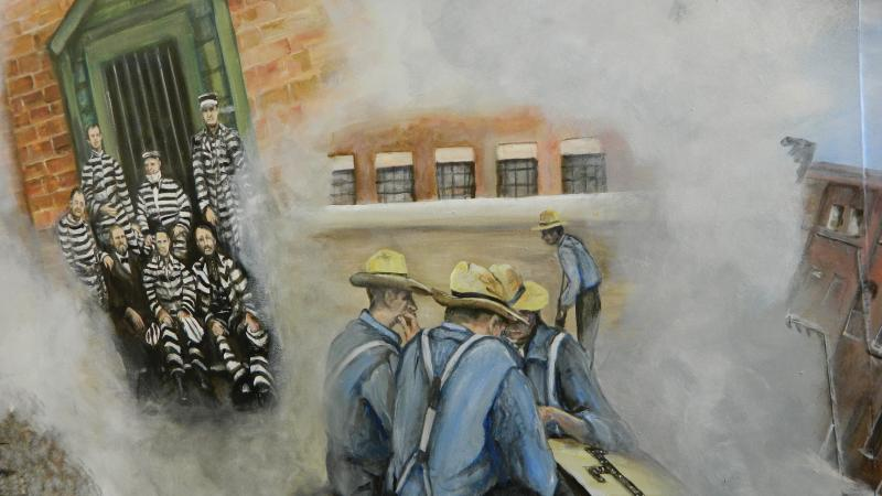 Mural showing prisoners in striped uniforms on the left, and a group of blue shirted men huddled around a table on the right