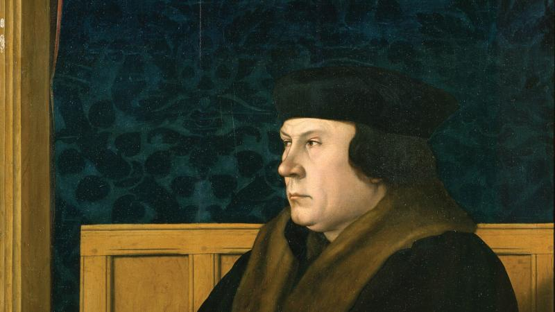 Color painting of Thomas Cromwell in regal dress, sitting at a desk draped with an elegant green tablecloth.