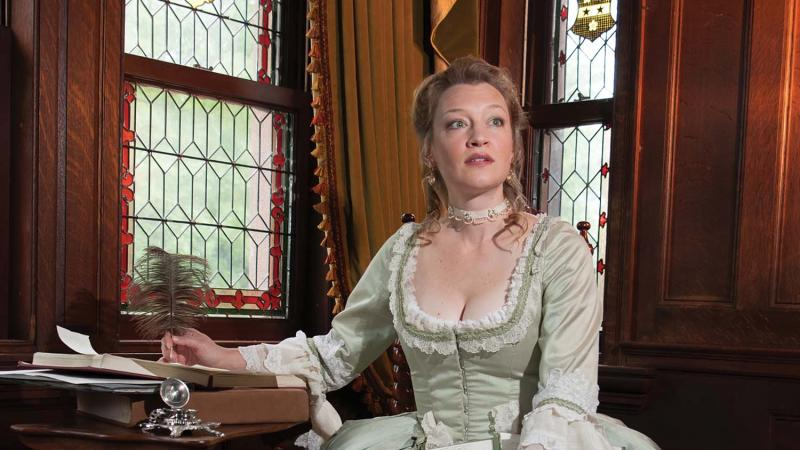 Stauffer in a green, 1800's era dress, sitting at a desk