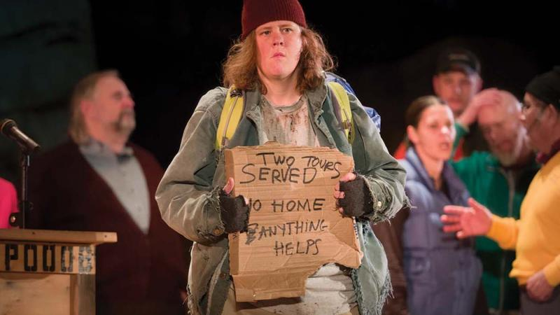 "An actor holds up a sign reading ""served two tours, no home, anything helps"" during a scene"