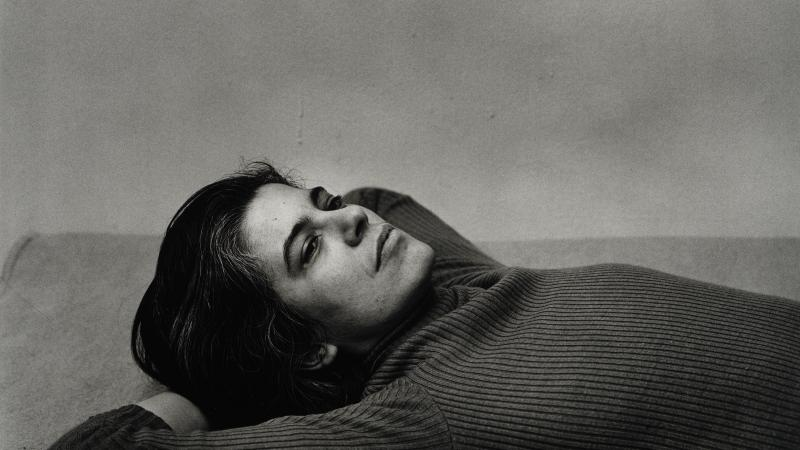 black and white photo of Sontag, lying down with her hands underneath her head