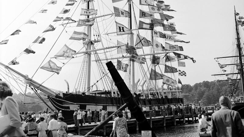 black and white photo of the Charles W Morgan ship, surrounded by people with flags fluttering