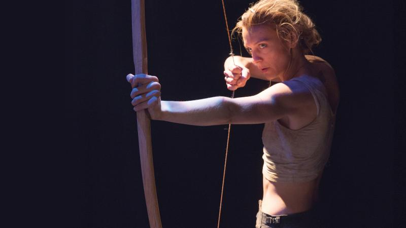 Color photo of a woman pulling an arrow back on her bow.