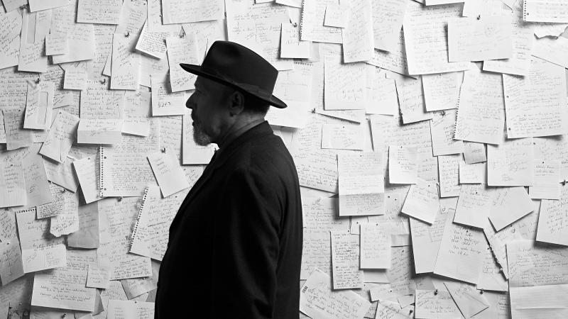 Black and white side portrait of August Wilson standing before a wall covered by letters that have been pinned onto it.