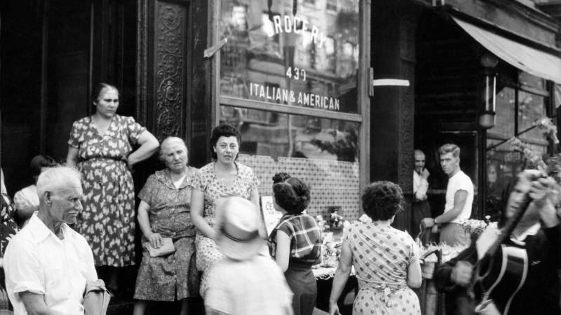 Black and white photo of Italian immigrants in Little Italy congregating outside a storefront.