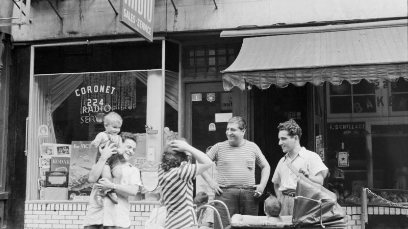 Black and white photo of Italian immigrants standing outside a storefront. One man is holding a baby up in the air, while a woman and two other men stand around a baby stroller.