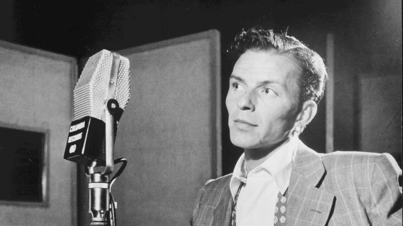 Black and white photo of Frank Sinatra standing before a microphone on stage.