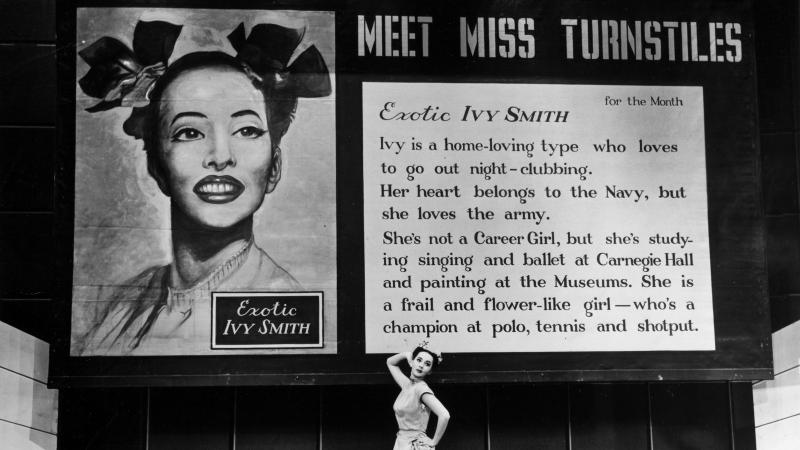 "Black and white photo of Sono Osato standing before a large billboard ad for ""Miss Turnstiles."""