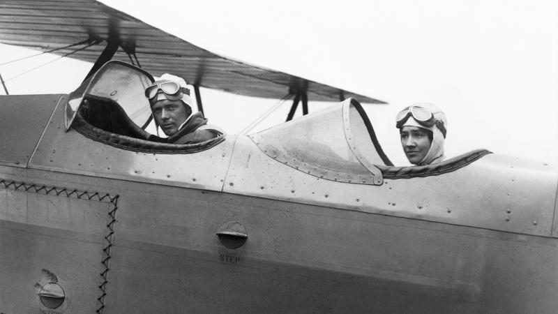 Black and white photo of two individuals sitting in their respective cockpit seats in a plane.