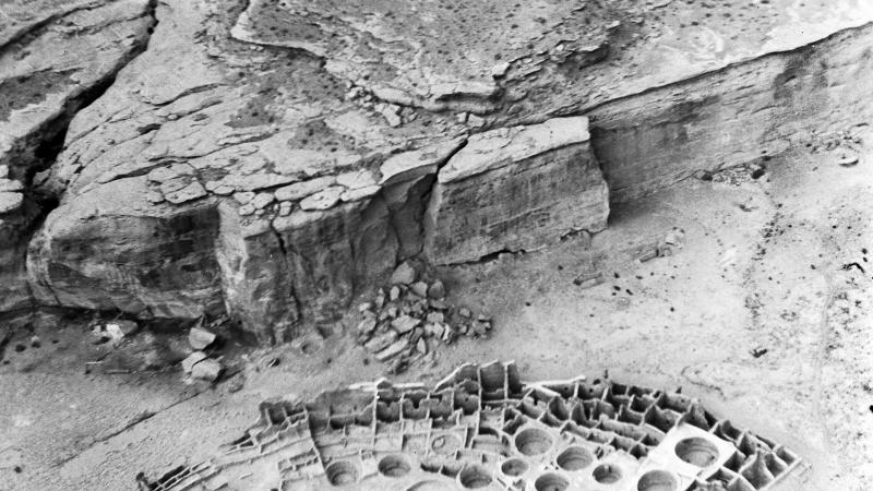 Black and white aerial photo of archaeological ruins in a desert canyon-like area.