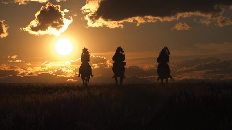 Color photo of three men on horseback riding into the glimmering sunset.