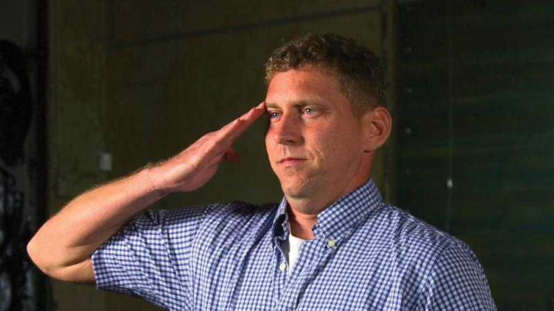 Color photo of a man wearing a blue shirt saluting an audience.