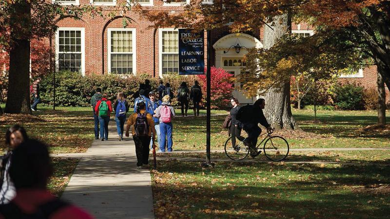 Students walking and biking in a green part of campus