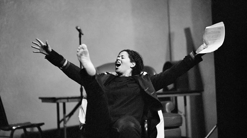 Black and white photo of Anna Deavere Smith acting on stage and making an exclamation.