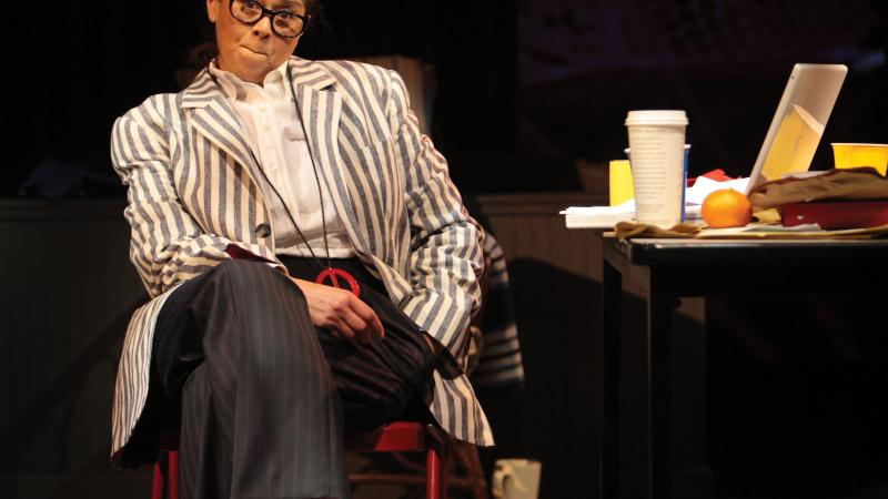 Color photo of Anna Deavere Smith playing a character on stage, sitting in a chair with her legs crossed.