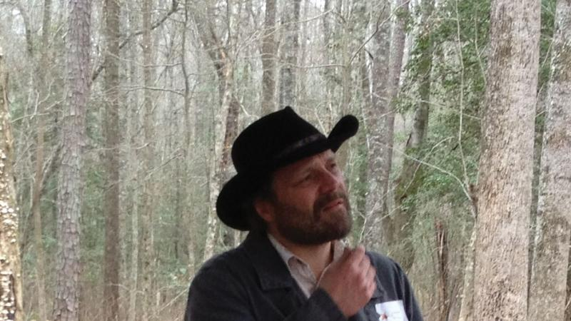 Color photo portrait of Daniel Sayers wearing a black cowboy hat and jacket.