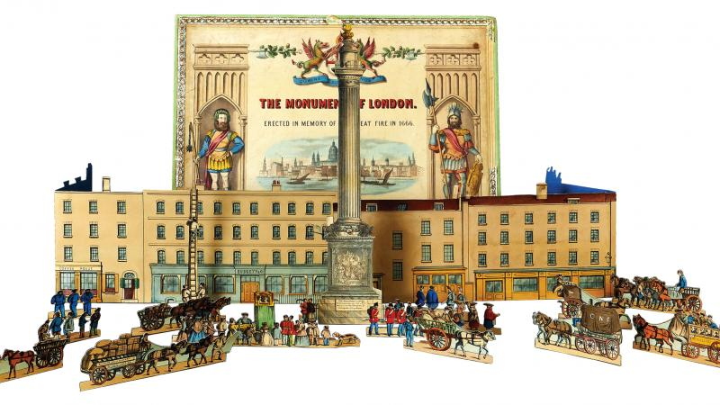 Color photo of a toy set of the Monument of London, including figurines and a building.