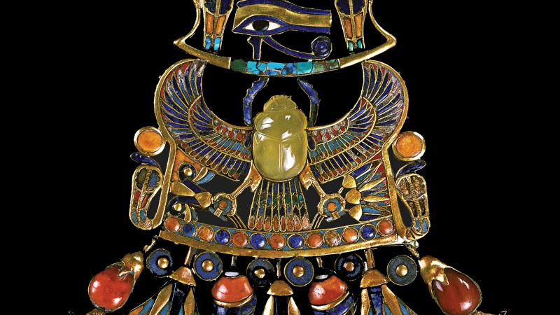 Photo of a golden pectoral body ornament with a yellow-green scarab at its center.