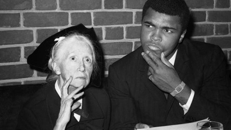 Black and white photo of poet Marianne Moore seated next to Mohammed Ali, who stares, intrigued, fingers on his chin, toward something else in the room.